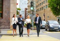 Fyra lyckade affärspersoner som korsar gatan i staden Royaltyfri Bild