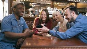Fyra lyckliga caucasian vänner som tillsammans använder den smarta telefonen i stången, bar stock video