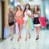 Fyra lyckliga kvinnor som går tillbaka från shopping royaltyfria foton