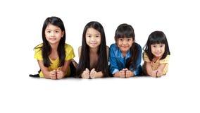 Fyra lyckliga lilla asiatiska flickor som lägger på golvet royaltyfria foton