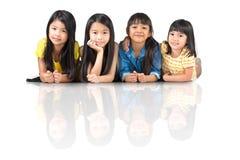 Fyra lyckliga lilla asiatiska flickor som lägger på golvet Arkivbild