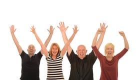 Fyra lyckliga personer som lyfter armar i luften arkivbilder