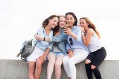 Fyra lyckliga unga studentflickor som gör utomhus- selfie royaltyfria bilder