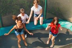Fyra lyckliga vänner som studsar på den utomhus- trampolinen fotografering för bildbyråer
