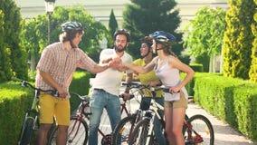 Fyra lyckliga vänner som utomhus staplar händer arkivfilmer