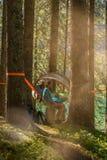 Fyra lyckligt hängande tält för man som och för kvinna campar i skogträn under solig dag nära sjön Grupp av vänfolksommar arkivfoto