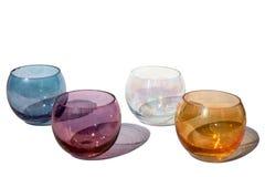 Fyra mångfärgade tappningrundaexponeringsglas på en vit bakgrund med härliga kulöra skuggor i solljus isolerat slut upp royaltyfri foto