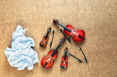 Fyra musikaliska orkesterinstrument för rad: fiol, violoncell, kontrabas, altfiol och skrynklig notblad som ligger nära dem Arkivfoton