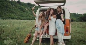 Fyra nätta unga damer som tar selfie som sitter på den retro skåpbilen, i mitt av fältet 4K lager videofilmer