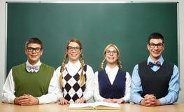 Fyra nerds framme av svart tavla Royaltyfri Foto