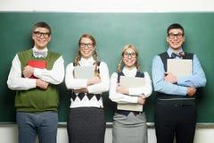 Fyra nerds framme av svart tavla Arkivbild