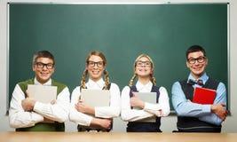Fyra nerds som rymmer böcker Royaltyfri Fotografi