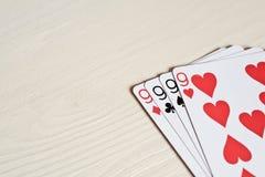 fyra nio pokerhänder som spelar kort på en ljus skrivbordbakgrund Royaltyfria Foton