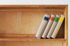 Fyra nya böcker på en trähylla royaltyfri foto
