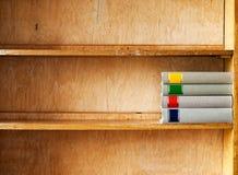 Fyra nya böcker på en trähylla Royaltyfri Fotografi