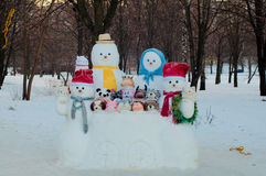 Fyra olika formatdressedsnowmen och djur som utomhus göras av snö nära träd i vinter Royaltyfri Fotografi