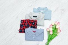 Fyra olika skjortor och en bukett av tulpan Trendig conce Royaltyfri Bild