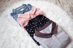 Fyra olika skjortor på vit päls, sortiment för begreppsframsida för skönhet blå ljus kvinna för makeup för mode Arkivbild