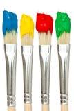 Fyra paintbrushes med färgmålarfärger Arkivfoton
