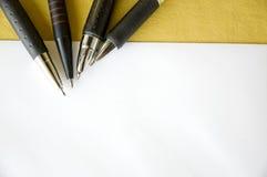 Fyra pennor på tomt papper Arkivfoton