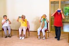 Fyra pensionärer som har gyckel under övningsgrupp royaltyfri foto