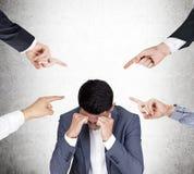 Fyra personer klandrar en stressad asiatisk affärsman Arkivfoto