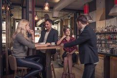 Fyra personer, liten grupp människor som inomhus talar, coffee shop Royaltyfri Bild