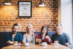 Fyra personer som sitter på tabellen i ett kafé Royaltyfri Fotografi