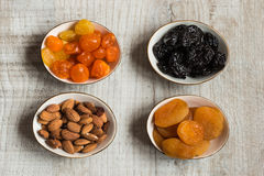 Fyra plattor med torkade frukter på träbakgrund: torkade mandariner, katrinplommoner, aprikors och mandlar Royaltyfri Fotografi