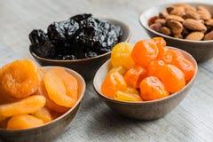 Fyra plattor med torkade frukter på träbakgrund: torkade mandariner, katrinplommoner, aprikors och mandlar Royaltyfri Bild