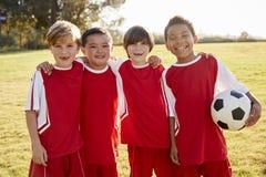 Fyra pojkar i ett fotbollslaginnehav klumpa ihop sig och att le till kameran royaltyfri foto