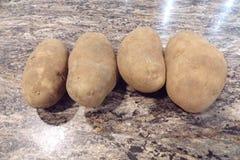 Fyra potatisar som är klara för att laga mat arkivbild