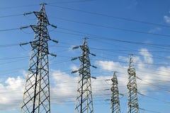 Fyra pyloner av de elektriska kablarna för hög spänning i kraftverk arkivfoton
