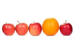 Fyra röda äpplen och apelsin Arkivfoto