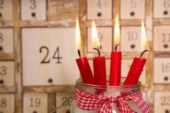 Fyra röda brinnande adventstearinljus med kalendern Arkivfoton