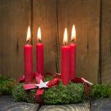 Fyra röda brinnande adventstearinljus på en krans Royaltyfria Foton