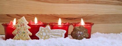 Fyra röda stearinljus och julkakor Royaltyfria Bilder