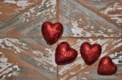 Fyra röda valentinhjärtor på en grov träbrädebakgrund arkivfoton