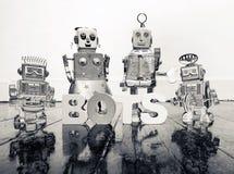 Fyra retro robotleksaker och ordet BOTS på a arkivbilder
