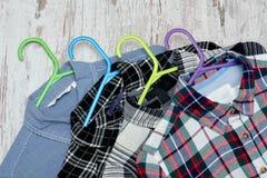 Fyra rutiga skjortor på mång--färgade hängare trendigt begrepp Närbild Royaltyfri Foto