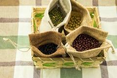 Fyra säckvävsäckar och gula bönor, svarta bönor, röda bönor och haricot vert Royaltyfri Foto