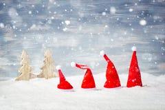 Fyra Santa Christmas hattar framme av snöstjärnor och träd Arkivfoto