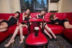 Fyra sexiga flickor på en röd soffa I inre royaltyfri fotografi