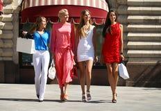 Fyra shoppa kvinnor som går på den röda fyrkanten i Moskva Arkivfoton