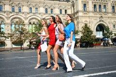 Fyra shoppa kvinnor som går på den röda fyrkanten i Moskva Arkivfoto