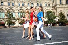 Fyra shoppa kvinnor som går på den röda fyrkanten i Moskva Royaltyfri Bild
