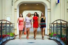 Fyra shoppa kvinnor som in går, shoppar Arkivbild