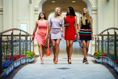 Fyra shoppa kvinnor som in går, shoppar Arkivbilder