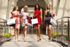 Fyra shoppa kvinnor som in går, shoppar Royaltyfria Bilder