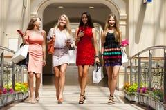 Fyra shoppa kvinnor som in går, shoppar Arkivfoto